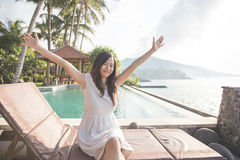 pretty girl raise her hands enjoying sunlight on tropical beach Stock Image