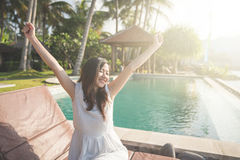 Pretty girl raise her hands enjoying sunlight on tropical beach Royalty Free Stock Image