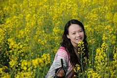 Pretty girl in rape flowers Stock Photography