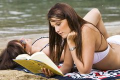 Pretty Girl reading a book. A beautiful girl wearing a bikini and reading a book on the beach Stock Photo