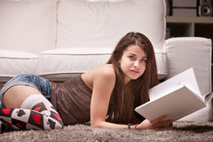 Pretty girl reading a book on the carpet Stock Image