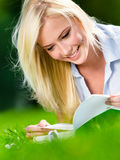 Pretty girl reading book on the grass Stock Photography