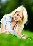 Pretty girl reading book on the green grass Royalty Free Stock Image