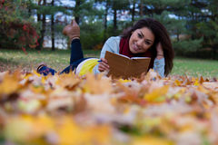 Pretty girl reading a book lying down on colourful leaves during Stock Photo