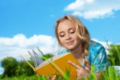 Pretty girl  reading book outdoors Stock Image