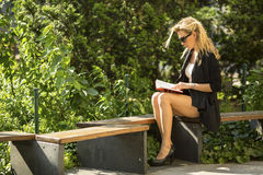 Pretty  girl reading a book sitting on a Park bench. Royalty Free Stock Images