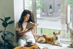 Pretty girl reading book stroking shiba inu dog relaxing on window sill in cafe