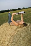 Pretty Girl reading Magazine on farm. Pretty girl reading magazine on bale of hay at farm royalty free stock photography