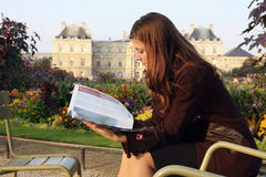 Pretty girl reading magazine in Luxembourg garden. (Paris). Late afternoon sun. Autumn colors. Luxembourg palace in background Royalty Free Stock Images