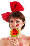 Pretty girl with a red bow and lollipop in mouth in lipstick kisses Royalty Free Stock Photography