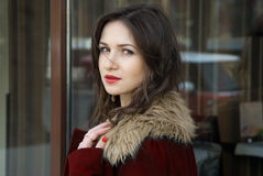Pretty girl in red coat and her expressive eyes Stock Image