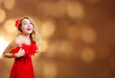 Pretty girl in red dress excited on bokeh lights. Picture of beautiful young lady in red dress surprised. Pretty girl excited on blurred bokeh party lights Stock Photos