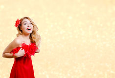 Pretty girl in red dress excited on bokeh lights. Picture of beautiful young lady in red dress surprised. Pretty girl excited on blurred bokeh party lights Royalty Free Stock Image