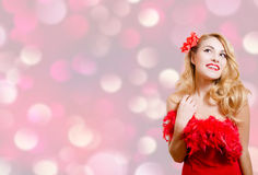 Pretty girl in red dress excited on bokeh lights. Picture of beautiful young lady in red dress surprised. Pretty girl excited on blurred bokeh party lights Royalty Free Stock Photography