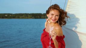 Pretty girl in red dress relaxing and drinking wine on sailing boat