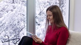 Pretty girl in red dress sitting on the windowsill and using tablet computer. Winter outside. Pretty girl in red dress sitting on the windowsill and using stock footage