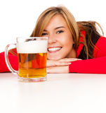Pretty girl in red drinking beer from the mug Royalty Free Stock Photos