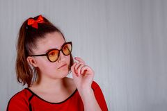 A pretty girl in red glasses and a on a gray background bit her lip royalty free stock photo