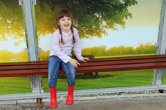 Pretty girl in red gumboots sits on bench and laughs Stock Photography