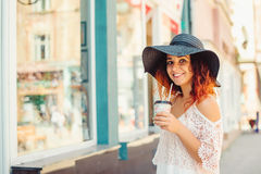 Pretty girl with red hair in a black hat is drinking take away coffee.Sunny summer day. City style. Girl looks at camera. Smile. Stock Image