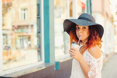 Pretty girl with red hair in a black hat is drinking take away coffee.Sunny summer day. City style.Girl wearing stylish summer dre Royalty Free Stock Photography