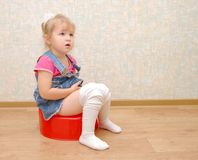 Pretty girl and red potty Royalty Free Stock Photo
