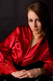 Pretty girl red robe black satin Stock Photo
