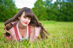 Pretty girl in red sarafan lies on green grass Stock Photo