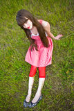 Pretty girl in red sarafan sit on green grass Royalty Free Stock Images