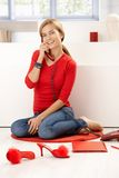 Pretty girl in red talking on phone at home Royalty Free Stock Images