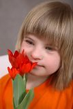 Pretty Girl with Red Tulips. A pretty young 9-year old girl with Downs Syndrome, holding a bunch of fresh red tulips stock photo