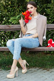 Pretty girl with red tulips sitting on the bench Royalty Free Stock Image