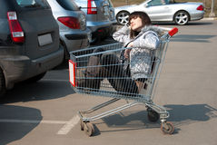 Pretty girl relaxes in a shopping cart Stock Photography