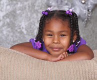 Pretty Girl Relaxes On Sofa. A pretty and happy little girl smiles and resting on sofa Royalty Free Stock Image