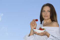 Pretty girl relaxing on balcony and eat red fresh. Strawberry Stock Image