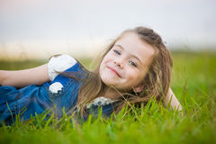 A pretty girl relaxing on the grass. A girl with a cheeky smile relaxing on the green grass Royalty Free Stock Image