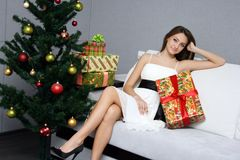 Pretty girl relaxing near the Christmas tree Royalty Free Stock Image