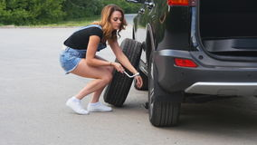Pretty girl replacing tyres. Pretty girl replacing summer tyres with winter tyres, before coming winter stock video