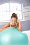 Pretty girl resting on fitball after workout Stock Images