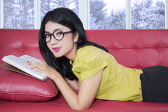 Pretty girl resting at home while reading book Royalty Free Stock Image