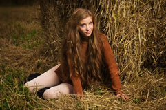 Pretty girl resting on straw bale Royalty Free Stock Photo