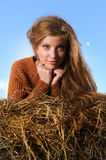 Pretty girl resting on straw bale Stock Images
