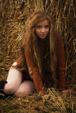 Pretty girl resting on straw bale Stock Photo