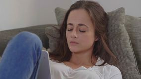 Pretty girl rests on the couch with her tablet computer. Videoclip stock video footage