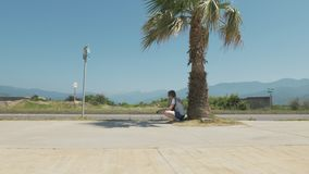 Pretty girl rests near the palm tree. Batumi, Georgia.  stock footage