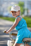 Pretty girl riding bicycle, close-up Stock Photography