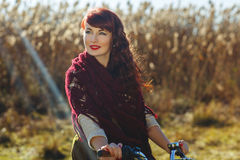 Pretty girl riding bicycle in field Stock Photos