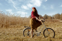 Pretty girl riding bicycle in field Stock Image