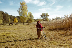 Pretty girl riding bicycle in field Stock Photography