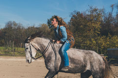 Pretty girl riding her grey horse Royalty Free Stock Photography
